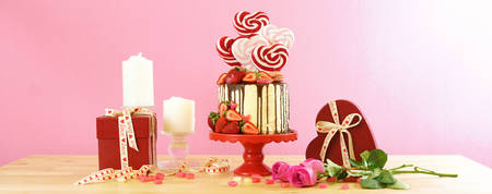 St Valentines Day on-trend candyland fantasy drip novelty cake decorated with heart shaped lollipops, candy and fresh strawberries.