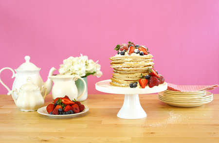 Shrove Pancake Tuesday, last day before Lent, stack of pancakes cake prepared with layers of whipped cream and fresh berries. Banco de Imagens