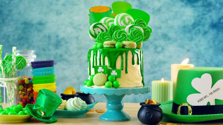 St Patrick's Day theme candyland novelty drip cake and party table. 免版税图像 - 116930596