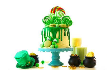 St Patricks Day party table with lollipop candy land drip cake on white Stockfoto
