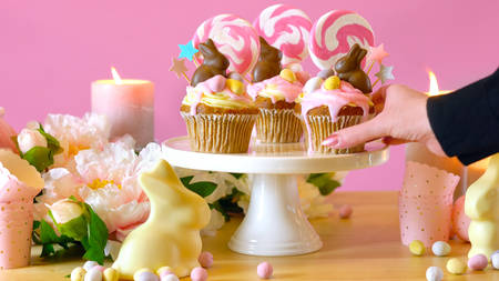 Easter theme candy land drip cupcakes decorated with chocolate bunnies in party table setting.