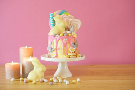 On-trend Easter theme candy land drip cake decorated with lollipops, candy eggs and white chocolate bunny in party table setting. 版權商用圖片