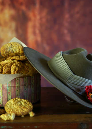 Traditional ANZAC biscuits for ANZAC Day and Remembrance Day in vintage style setting with Australian army slouch hat with copy space. Stock Photo
