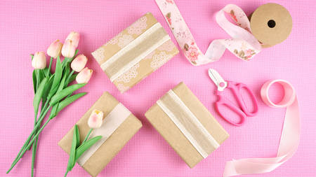 Gifts wrapped in kraft paper and pink ribbons overhead flat lay for Mothers Day, birthday or Valentines Day celebrations.