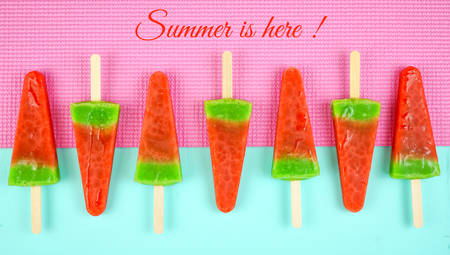 Watermelon flavored summer theme ice cream popsicles on pink and blue background with Summer is Here greeting text.. Reklamní fotografie