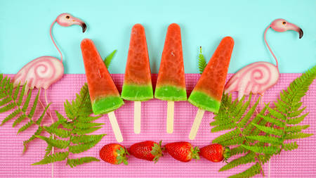 Watermelon flavored summer theme ice cream popsicles on pink and blue background. Reklamní fotografie