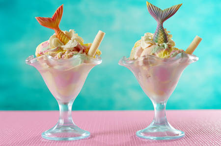 Mermaid sea theme rainbow ice cream sundaes with mermaid tails and candy shells and turtles, on pink and blue background. Reklamní fotografie