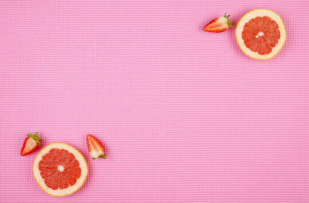 Summertime theme background with ruby grapefruit and strawberries on pink backdrop, with copy space.