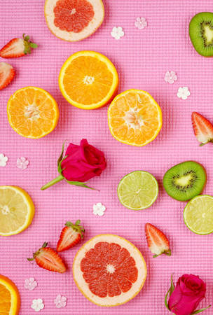 Summertime theme background with fruit, citrus and flowers on pink backdrop.