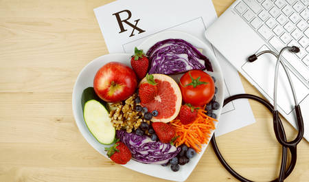 Prescription for good health overhead with stethoscope, healthy fresh food and exercise equipment, with copy space.
