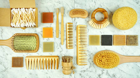 Zero-waste, plastic-free household flatlay overhead with coconut fiber, bamboo and reusable bathroom and toiletries products.