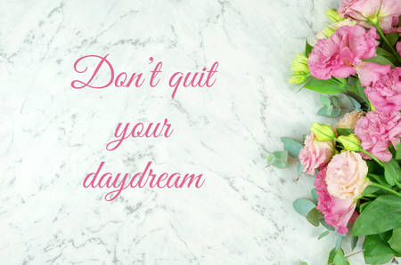 White marble texture  with pink flowers border frame and inspirational, Dont quit your daydream, text greeting.