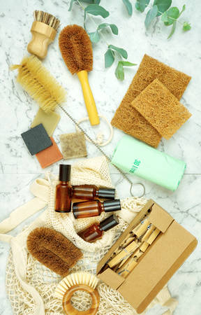 Zero-waste, plastic-free household flatlay overhead with coconut fiber, bamboo and reusable laundry and eco-friendly cleaning products.