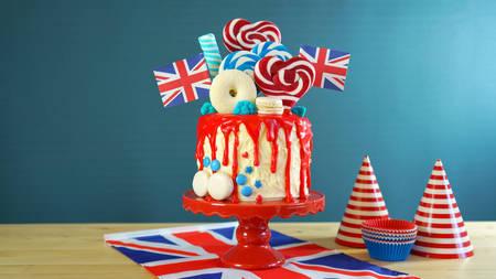 英国流行糖果乐园幻想滴蛋糕与红色,白色和蓝色装饰,棒棒糖和旗帜与复制空间。