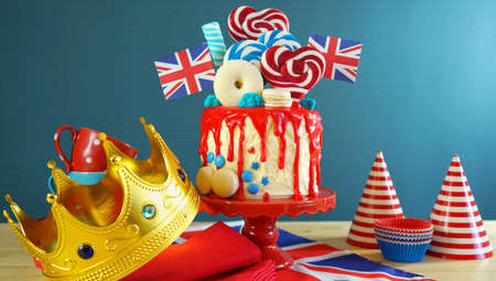 英国流行的糖果乐园梦幻滴油蛋糕,有红色、白色和蓝色的装饰,还有棒棒糖和旗帜。