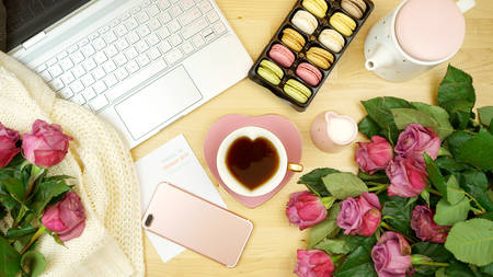 Feminine desk or workspace coffee break time overhead flatlay with modern hi tech laptop and scattered roses.
