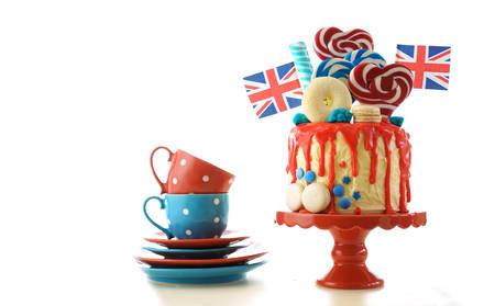 英国流行糖果乐园梦幻滴油蛋糕,红色,白色和蓝色装饰,棒棒糖和旗帜在白色的背景。