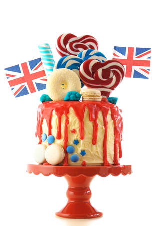 UK on-trend candyland fantasy drip cake with red, white and blue decorations, lollipops and flags on white background.