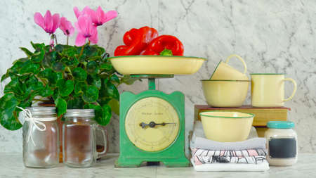 Vintage kitchen scale decor with farmhouse style kitchenware, with stack of old books, mason jars, vintage tin crockery and potted pink cyclamens. Reklamní fotografie