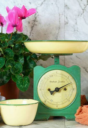 Vintage kitchen scale decor with farmhouse style kitchenware, with stack of old books, mason jars, vintage tin crockery and potted pink cyclamens. 写真素材