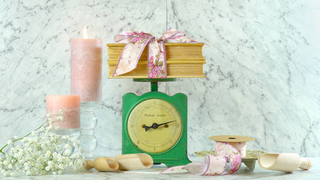 Vintage kitchen scale decor setting with porcelain jug of gypsophila flowers, candles, floral ribbons and old books.