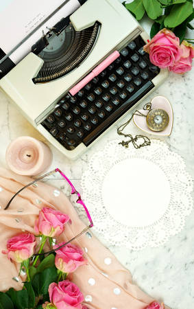 Romantic vintage feminine writing scene, tea break with old typewriter and pink roses on marble table top down overhead.