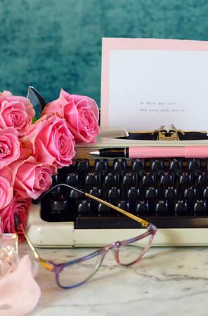 Romantic vintage feminine writing scene, tea break with old typewriter and pink roses.