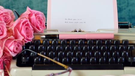Romantic vintage feminine writing scene, tea break with old typewriter and pink roses.