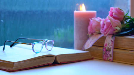 Nostalgia scene relaxing by the window on a cold rainy day with old books and reading glasses. Imagens