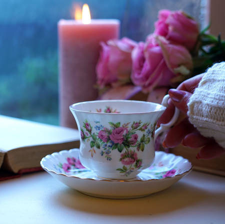 Nostalgia scene relaxing by the window on a cold rainy day with old books and cup of tea. Imagens
