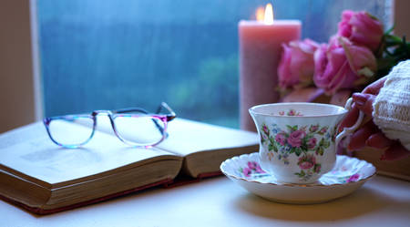 Nostalgia scene relaxing by the window on a cold rainy day with old books and cup of tea. Reklamní fotografie