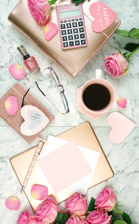 Ultra feminine pink desk workspace with rose gold accessories on white marble