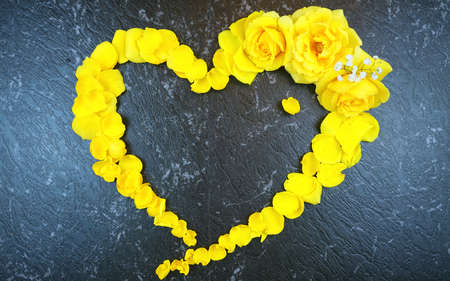 Love heart border made from fresh yellow roses and petals on black marble Stock Photo - 124972317