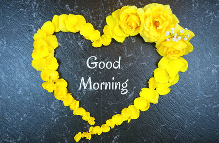 Good morning concept with text inside heart made from fresh yellow roses and petals on black marble Stock Photo