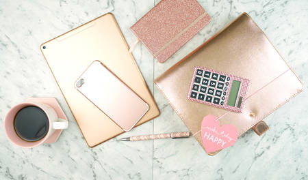 Feminine desk workspace with rose gold accessories on white marble table, flatlay overhead. Imagens