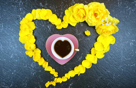 Good morning concept with coffee cup in heart made from fresh yellow roses and petals on black marble Stock Photo - 124972322