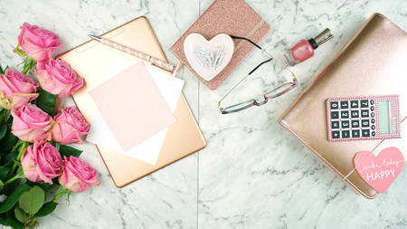 Ultra feminine pink desk workspace with rose gold accessories flatlay overhead. Imagens