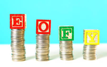 End of Financial Year and savings concept stacking coins with EOFY building blocks. Stock Photo