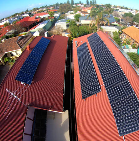 Multiple modern solar panels on domestic red roof in suburbs on sunny day, taken in South Australia.