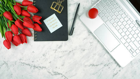 Modern stylish feminine desk or workspace coffee break with high tech touchscreen laptop and red female accessories, with copy space Banco de Imagens