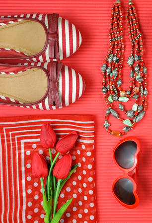 Red feminine accessories travel shopping preparation concept with shoes, bag, scarf and lipstick.
