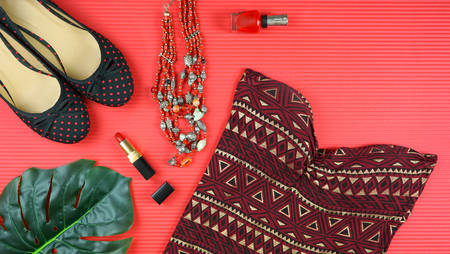 Summer vacation concept flatlay with summer dress and feminine accessories on red background.