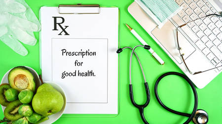 Prescription for good health overhead stop motion with doctors desk, rx form, stethoscope, healthy fresh food on symbolic green background. 写真素材