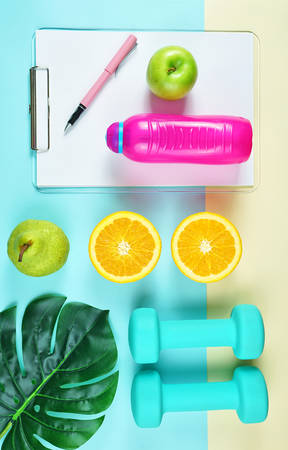 Health and fitness concept flat lay with exercise equipment on modern colorful background.