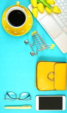 Online shopping concept with laptop, shopping cart, smart phone, calculator, coffee and accessories, overhead flat lay.