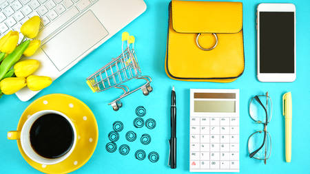 Online shopping concept with laptop, shopping cart, smart phone, calculator, coffee and accessories, overhead flatlay.