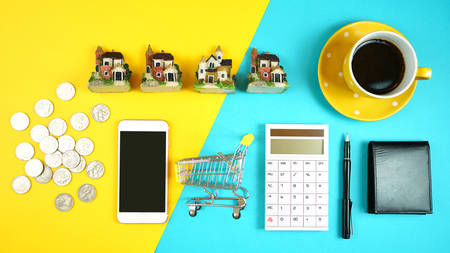 E-commerce real estate shopping, planning and financing for houses concept with miniature shopping cart and desk accessories.