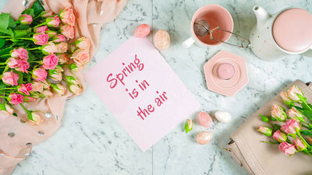 Welcoming Spring theme concept flat lay tea break with pink roses and female accessories on white marble background. 写真素材