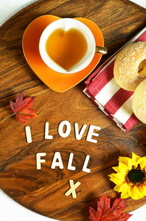 Autumn Fall theme flat lay overhead with sweater, bagels, cups of herbal tea and scattered maple leaves. 写真素材