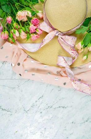 Welcoming Spring theme concept flat lay tea break with pink roses, sun hat and female accessories with copy space. 写真素材